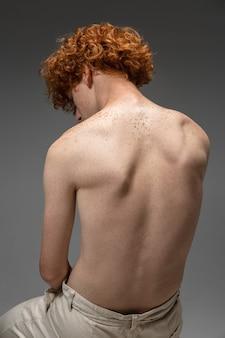 灰色の背景、スタジオの若い男。美しい赤毛