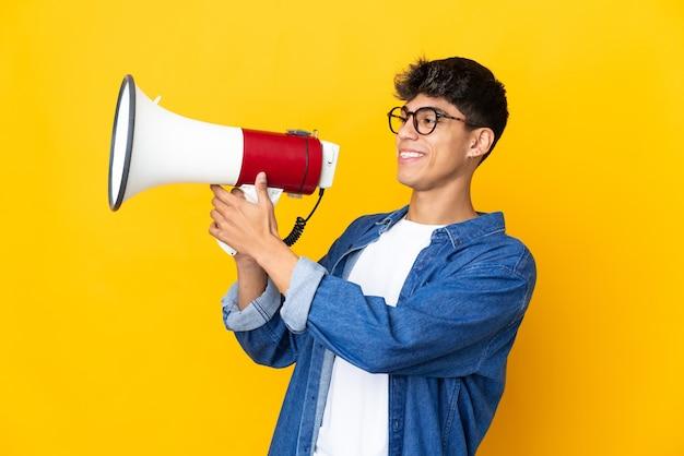 뭔가를 발표하기 위해 확성기를 통해 외치는 고립 된 노란색에 젊은 남자