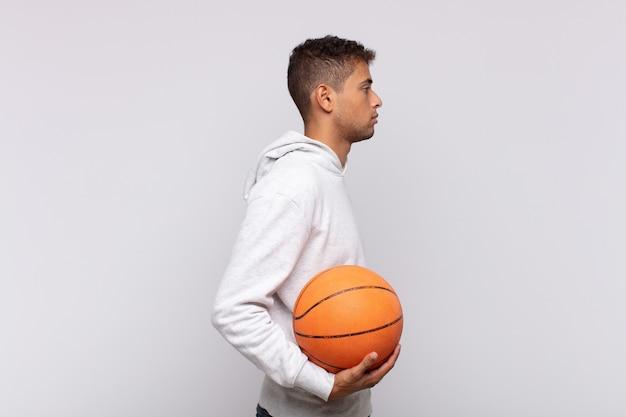 前方のスペースをコピーしようとしている、考えている、想像している、または空想にふけっている縦断ビューの若い男。バスケットコンセプト