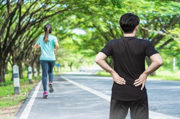 背中の痛みを持っている屋外でランニングロードの若い男。