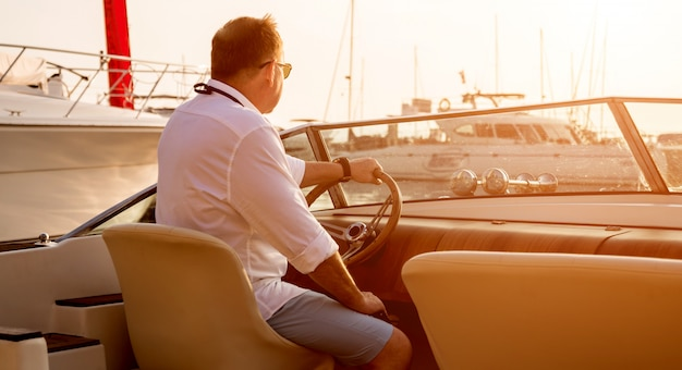 Молодой человек на парусной яхте. руки держат руль