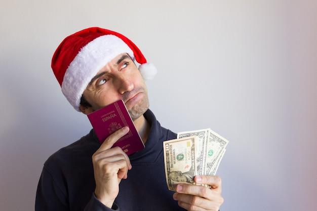 Молодой человек в шляпе санта-клауса держит паспорт и долларовый веер с задумчивым взглядом в сезон рождества