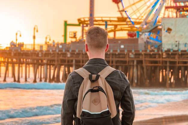 Молодой человек на пляже санта-моника перед оранжевым закатом в лос-анджелесе, калифорния