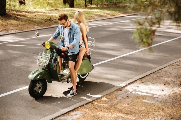 屋外の女性の友人とスクーターの若い男