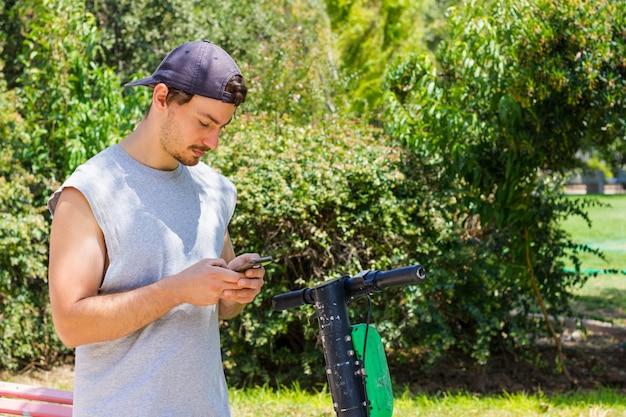公園で電動スクーターと携帯電話を見ているノースリーブシャツの若い男代替通勤輸送モバイルアプリの概念