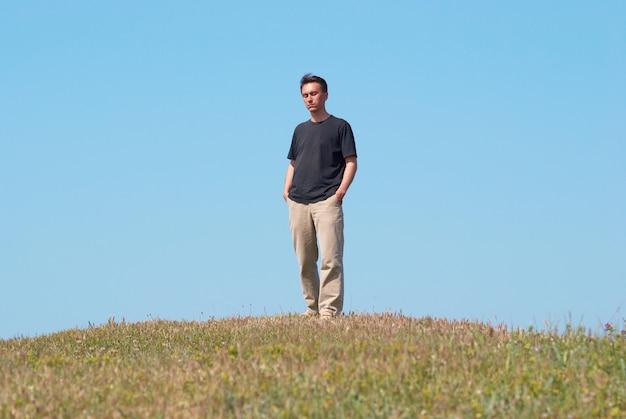 푸른 하늘 가진 잔디 필드에 젊은 남자