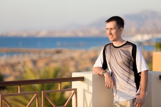 Молодой человек на террасе в солнечном свете