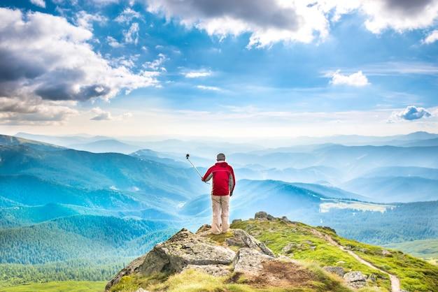 自撮り棒でスマートフォンで写真を撮る山の頂上に若い男