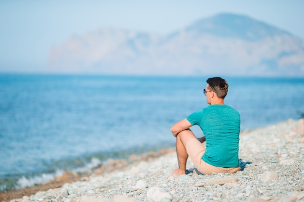 休暇中に白いビーチで若い男