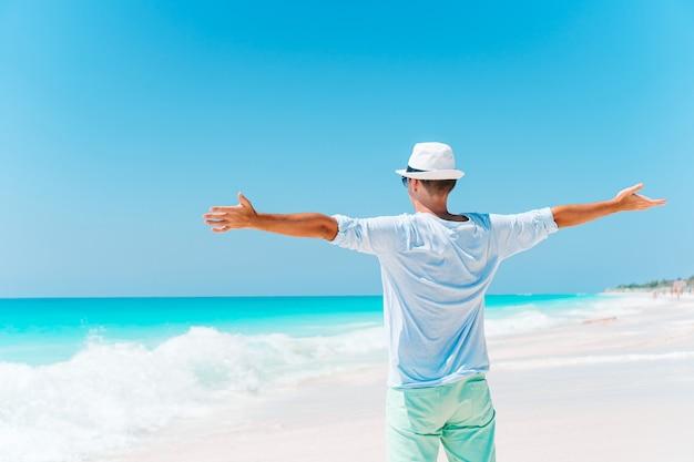 休暇中の白いビーチで若い男