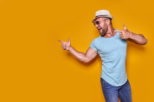 노란색 배경 위에 셔츠와 여름 모자를 쓰고 휴가 중인 젊은 남자가 손가락을 가리키며 성공...