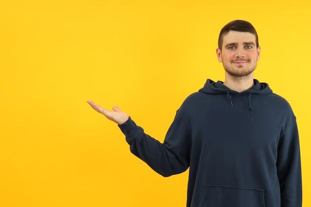 Молодой человек на желтом фоне, место для текста.