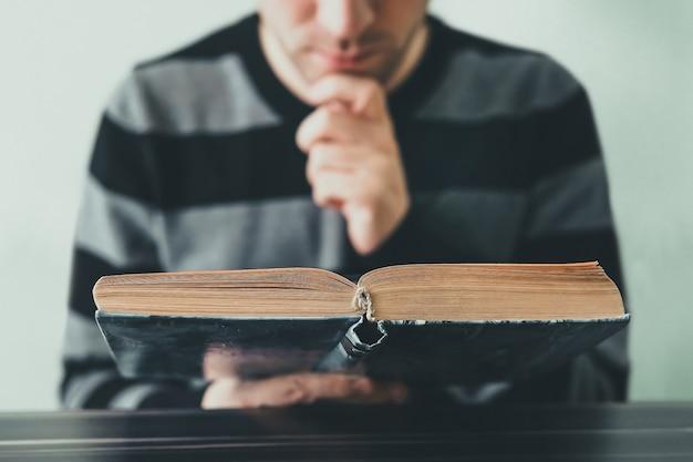 Молодой человек открытия и чтения книги, крупным планом. молодой человек внимательно, вдумчиво читает книгу, сидя за столом в библиотеке