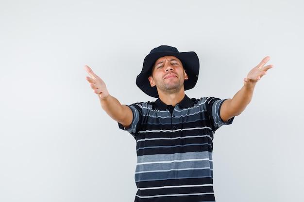 若い男は、tシャツ、帽子、フレンドリーに見える、正面図で抱擁のために腕を開きます。