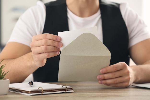 若い男が自宅に招待状で封筒を開く、クローズアップ