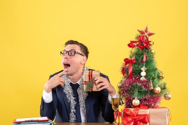 Молодой человек, открывающий рот, держит подарок, сидя за столом возле елки и подарки на желтом
