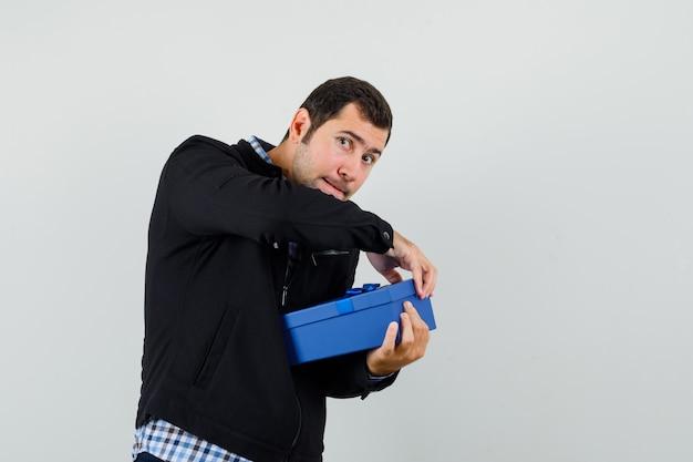 젊은 남자 셔츠, 재킷에 선물 상자를 열고 호기심을 찾고.