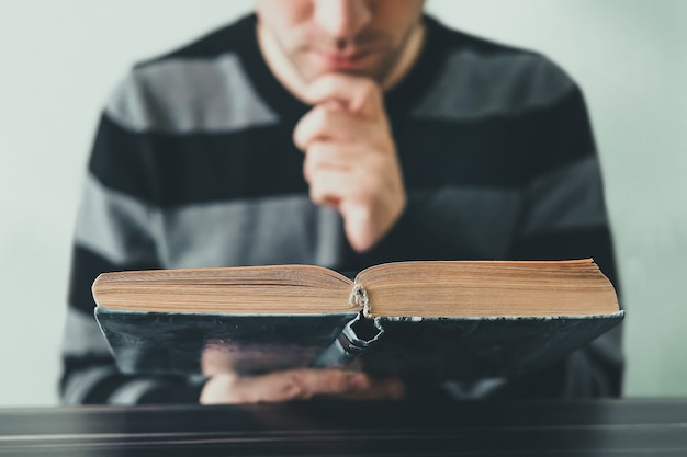 Young man opening and reading a book, close up. young adult carefully, thoughtfully reading a book sitting at the desk in the library