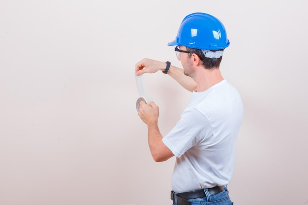 Young man opening roll of duct tape in t-shirt, jeans, helmet and looking careful