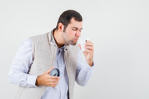 若い男がコーヒーカップをテイクアウトし、コーヒーを飲もうとしてベージュのジャケットの匂いを嗅ぎ、楽観的な正面図を探しています。