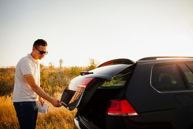 Молодой человек открывает багажник