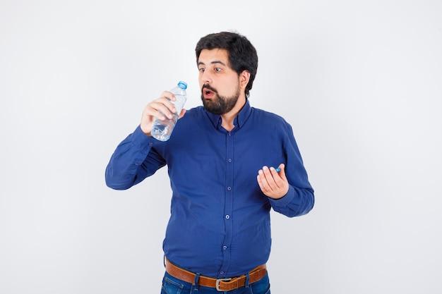 젊은 남자가 물병을 열고 파란색 셔츠와 청바지에 물을 마시고 놀란, 전면보기를 찾고 있습니다.