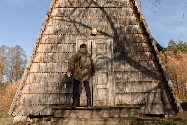 A young man opens the door if a wooden house. the concept of adventure and new discoveries.