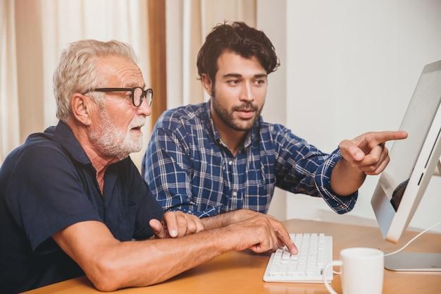 Молодой человек или сын учат своего деда, пожилого отца, который учится пользоваться компьютером дома.