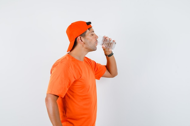 Giovane uomo in maglietta arancione e berretto in acqua potabile