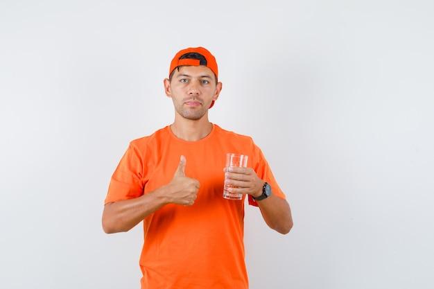 Giovane in maglietta arancione e berretto che tiene il bicchiere d'acqua con il pollice in su