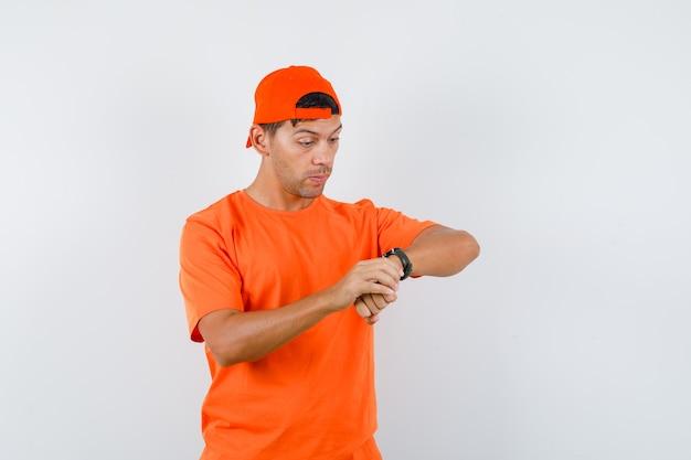Giovane uomo in maglietta arancione e berretto guardando l'orologio e guardando preoccupato