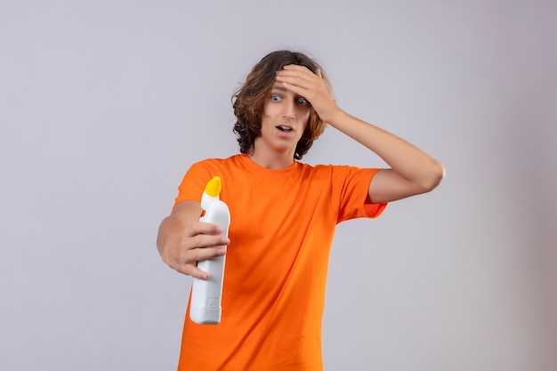 Young man in orange t-shirt holding bottle of cleaning supplies looking at it surprised touching head with hand standing over white background