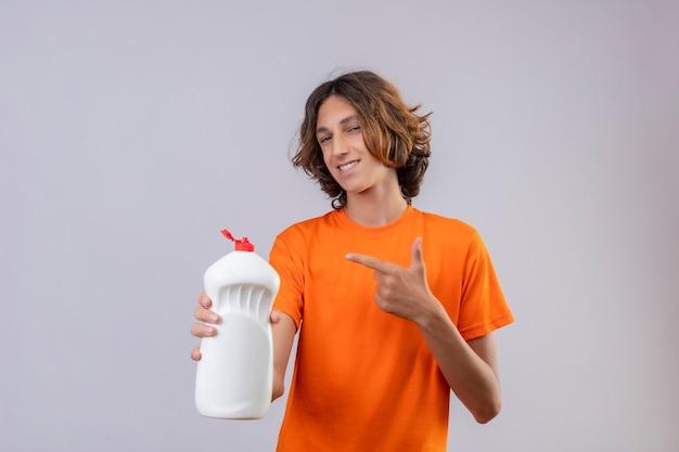Giovane uomo in maglietta arancione che tiene una bottiglia di prodotti per la pulizia che punta con il dito ad esso guardando la fotocamera con un sorriso fiducioso in piedi su sfondo bianco
