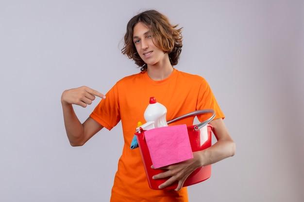 Giovane uomo in t-shirt arancione tenendo la benna con strumenti di pulizia puntando il dito verso di essa guardando la telecamera sorridendo allegramente in piedi su sfondo bianco
