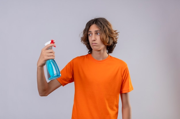 Young man in orange t-shirt holding cleaning spray looking at it with sad expression on face standing over white background