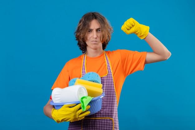 Giovane uomo in maglietta arancione che indossa un grembiule e guanti di gomma che tiene bacino con strumenti di pulizia alzando il pugno con sguardo fiducioso rallegrandosi del suo successo e della vittoria in piedi su bac blu