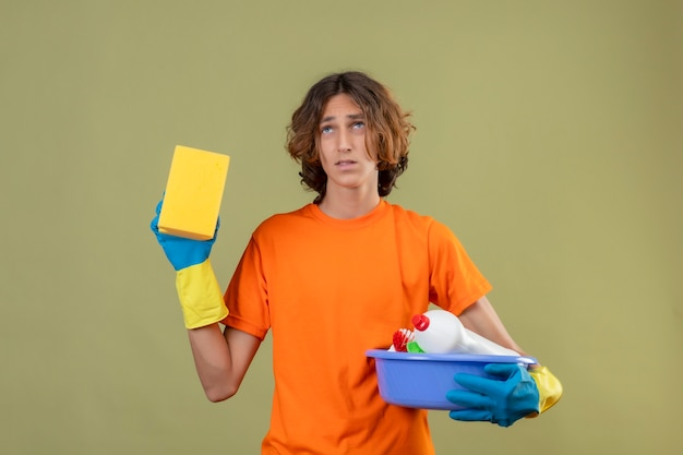 Young man in orange t-shirt wearing rubber gloves holding basin with cleaning tools and sponge looking up with sad expression on face standing over green background