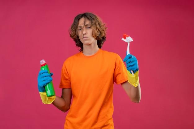 Giovane uomo in maglietta arancione che indossa guanti di gomma tenendo una bottiglia di prodotti per la pulizia e spazzola per strofinare guardando la telecamera scontento in piedi su sfondo rosa