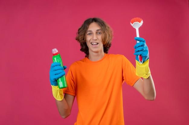 Giovane uomo in maglietta arancione che indossa guanti di gomma tenendo una bottiglia di prodotti per la pulizia e spazzola per strofinare guardando la telecamera sorridendo allegramente felice e positivo in piedi su sfondo rosa