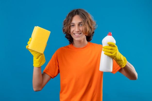 Giovane uomo in maglietta arancione che indossa guanti di gomma tenendo una bottiglia di prodotti per la pulizia e spugna guardando la telecamera sorridendo allegramente in piedi su sfondo blu