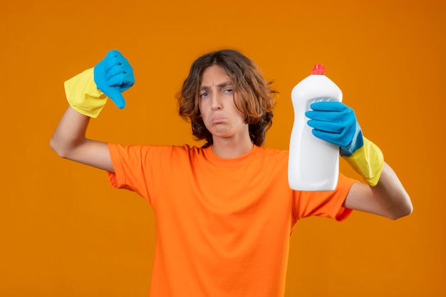 Young man in orange t-shirt wearing rubber gloves holding bottle with cleaning supplies showing thumbs down with sad expression on face standing over yellow background