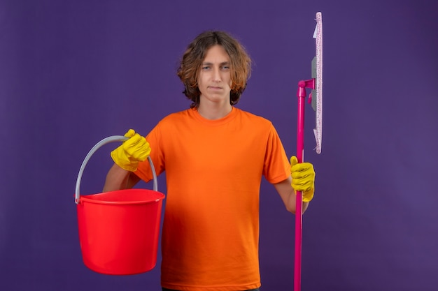 Young man in orange t-shirt wearing rubber gloves holding bucket and mop looking at camera with confident serious expression standing over purple background