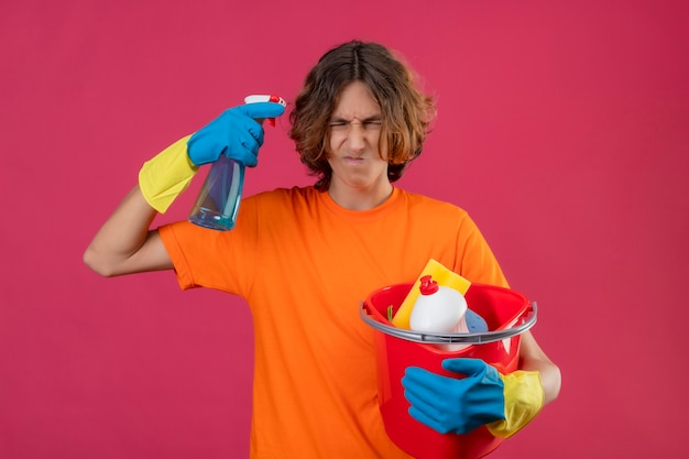 Young man in orange t-shirt wearing rubber gloves holding bucket with cleaning tools and cleaning spray looking annoyed and bothered standing over pink background