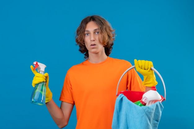 Giovane uomo in maglietta arancione che indossa guanti di gomma tenendo la benna con strumenti di pulizia e spray per la pulizia guardando la telecamera sorpreso in piedi su sfondo blu