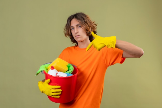 Young man in orange t-shirt wearing rubber gloves holding bucket with cleaning tools pointing with finger to it looking t camera with confident and serious facial expression standing over gre
