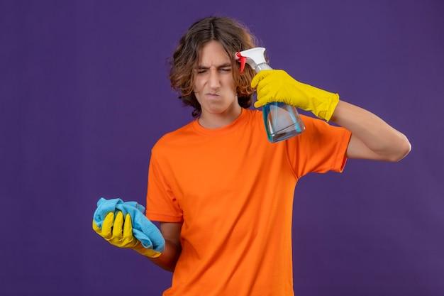 Giovane uomo in maglietta arancione che indossa guanti di gomma tenendo spray per la pulizia e rug guardando la telecamera scontento stanco e annoiato in piedi su sfondo viola