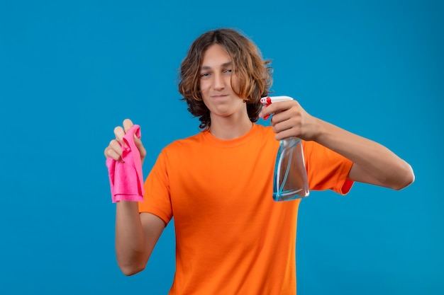 Young man in orange t-shirt wearing rubber gloves holding cleaning spray and rug looking at camera with confident smile ready to clean standing over blue background