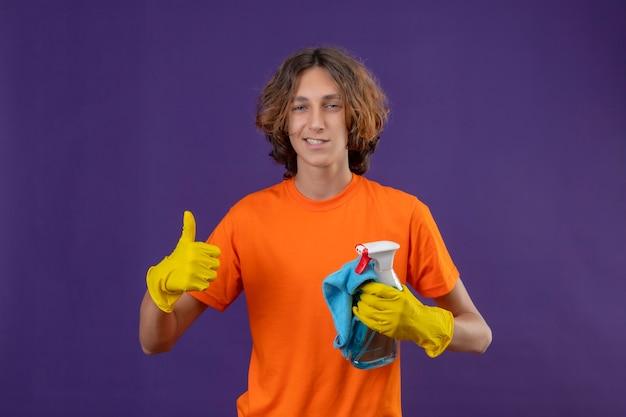 Giovane uomo in maglietta arancione che indossa guanti di gomma tenendo spray per la pulizia e rug guardando la telecamera con un sorriso fiducioso che mostra i pollici in su pronto per pulire in piedi su sfondo viola