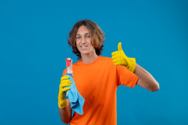 Young man in orange t-shirt wearing rubber gloves holding cleaning spray and rug looking at camera with confident smile showing thumbs up standing over blue background
