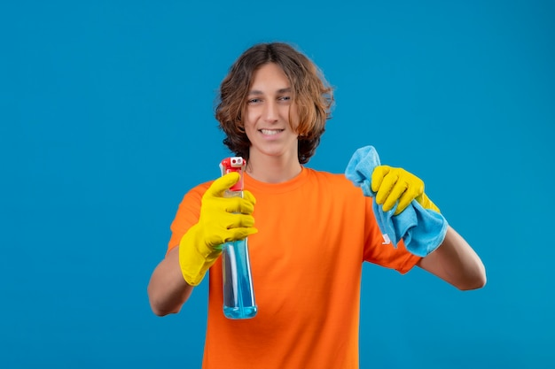 Young man in orange t-shirt wearing rubber gloves holding cleaning spray and rug looking at camera with confident smile standing over blue background